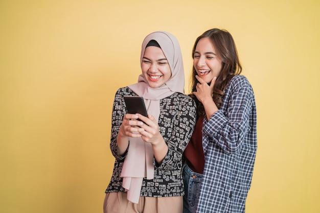 Felice due donne asiatiche usano un telefono cellulare e sono sorprese quando vedono lo schermo del telefono