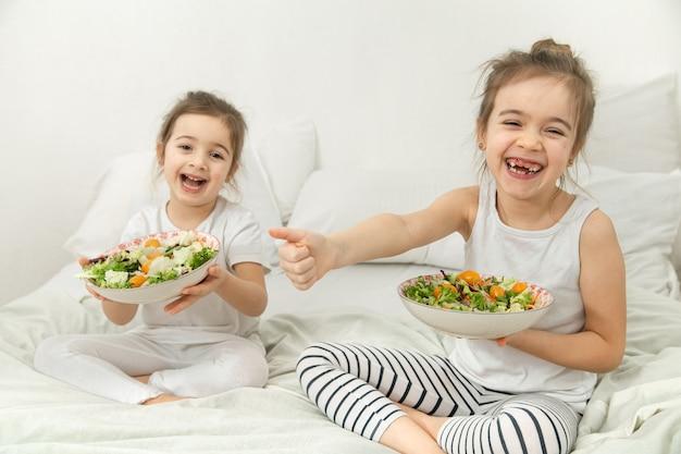 Due bambini carini felici che mangiano insalata di verdure in camera da letto sul letto. cibo sano per bambini e adolescenti.