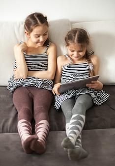 Due ragazze felici che guardano sullo schermo del tablet