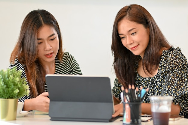 Felici due donne millenarie che lavorano insieme guardando il lavoro di squadra dello schermo del tablet