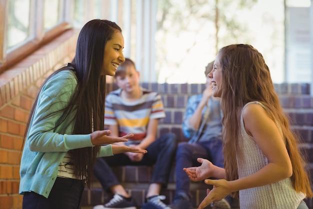 Felice due studentesse che interagiscono tra loro nel corridoio