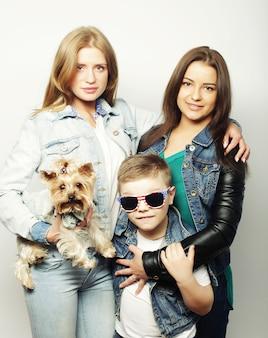 Felice due sorelle e fratello con yorkshire terrier