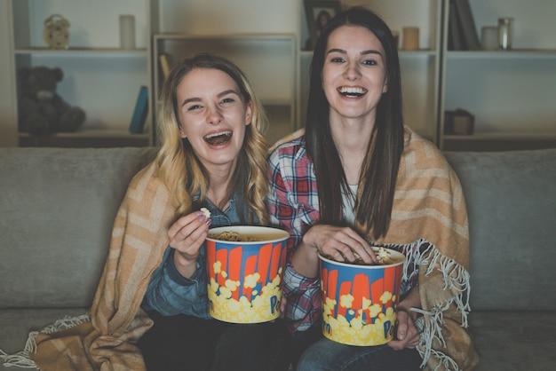 Le due donne felici con un popcorn guardano un film sul divano