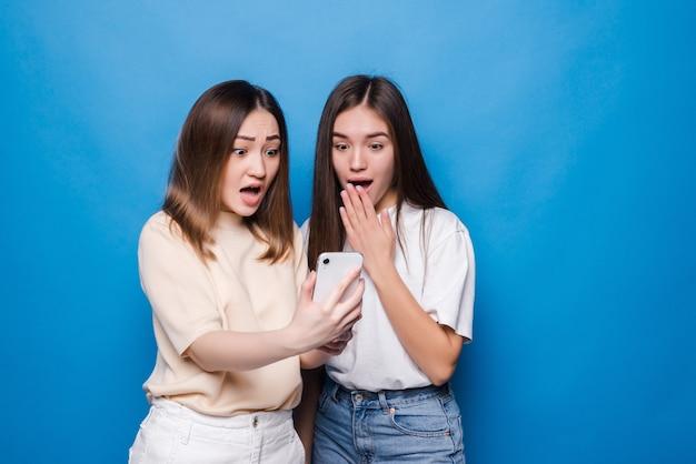 Felice due giovani ragazze ridendo e puntando il dito sullo schermo dello smartphone mentre si prende selfie isolato sopra la parete blu