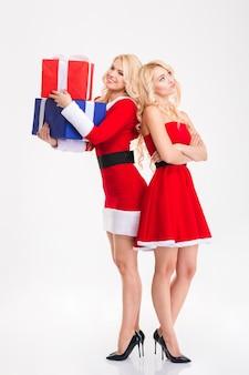 Felici e sconvolte belle sorelle gemelle in costumi rossi di babbo natale che condividono regali su sfondo bianco