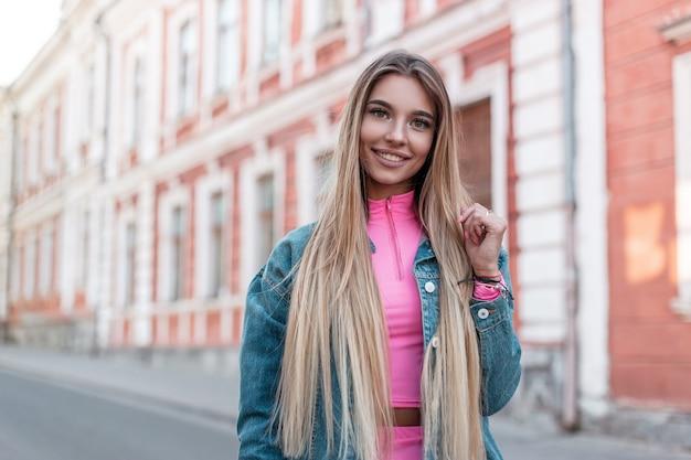 Felice giovane donna urbana con un sorriso positivo con capelli lunghi biondi in una giacca di jeans alla moda in un elegante top rosa posa vicino a un edificio bianco vintage in strada. la ragazza abbastanza allegra cammina nella città.