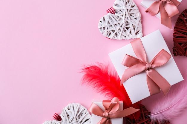 Modello di biglietto di auguri di buon san valentino. scatole regalo e cuori. copia spazio. piume rosse e bianche. vista dall'alto. lay piatto