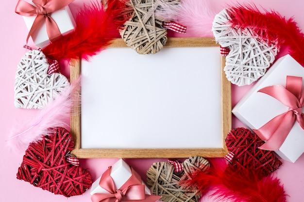 Modello di biglietto di auguri di buon san valentino. scatole regalo e cuori. copia spazio. piume rosse e bianche