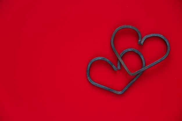 Buon san valentino. due cuori di metallo forgiato su sfondo rosso. lay piatto, copia dello spazio.