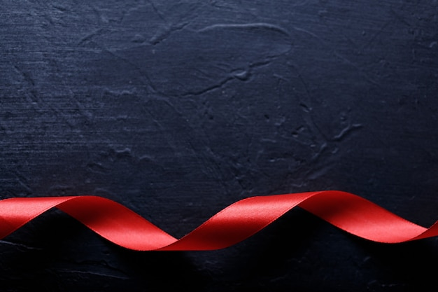 Buon san valentino. nastro rosso su sfondo di pietra nera. concetto di san valentino