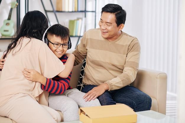 Felice ragazzo preteen vietnamita in nuovi auricolari che abbraccia i suoi genitori dopo averli ricevuti come regalo di compleanno