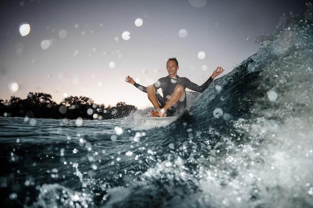 Wakesurfer felice che si siede sul bordo sull'onda di spruzzatura blu messa a fuoco