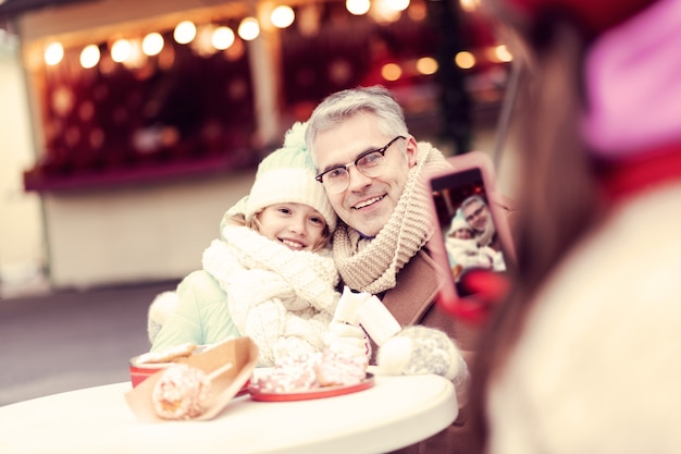 Siamo felici. ragazza allegra sensazione di felicità mentre posa sulla macchina fotografica con papà
