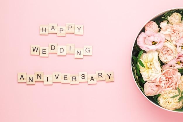 Iscrizione di anniversario di matrimonio felice sui quadrati di legno con lettere sullo sfondo rosa e