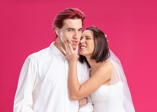 Felice sposi di sposo e sposa che si divertono a posare insieme felici innamorati insieme in piedi sul rosa
