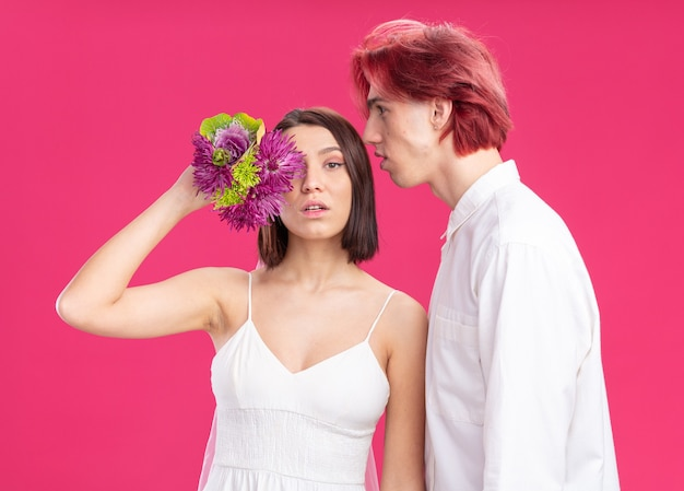 Felice sposi sposo e sposa in abito da sposa con fiori che si divertono insieme
