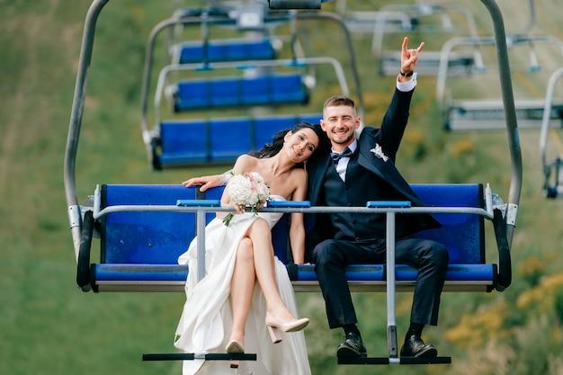 Teleferica felice di guida delle coppie di nozze dalla montagna.