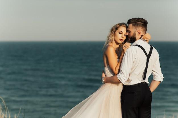 Coppie felici di nozze sulla spiaggia del mare.