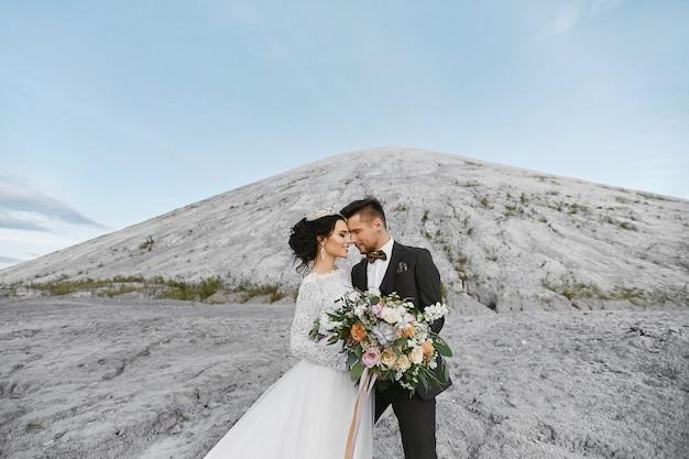Coppie felici di nozze che stanno all'aperto sopra il bello paesaggio con le montagne