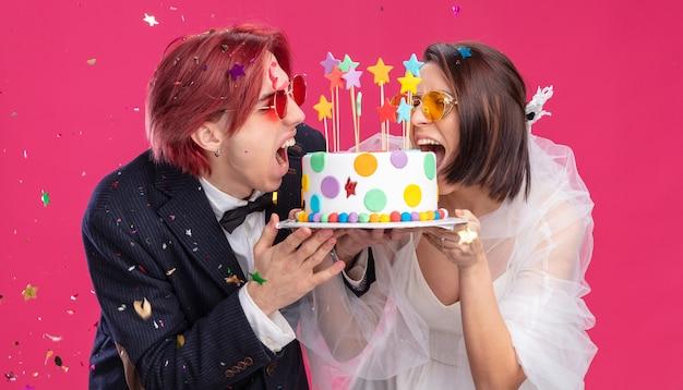 Felice sposi in abito da sposa con gli occhiali che tengono la torta nuziale felici ed emozionati sorridendo allegramente in piedi sul rosa