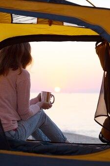 Buon fine settimana al mare - ragazza in tenda sulla spiaggia all'alba. paesaggio ucraino al mar d'azov, ucraina