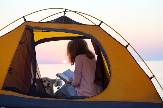 Buon fine settimana al mare - ragazza con un cane in tenda sulla spiaggia all'alba. paesaggio ucraino al mar d'azov, ucraina
