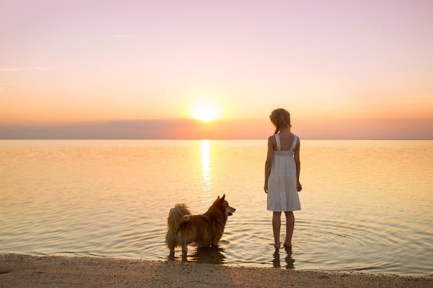 Buon fine settimana al mare - la bambina sta camminando con un cane corgi in riva al mare al tramonto. paesaggio ucraino al mar d'azov, ucraina