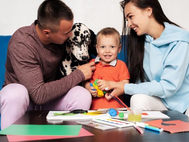 La famiglia bianca felice è felice e gioca in casa con un cane dalmata. mamma, papà e figlio ridono, dipingono e scolpiscono con la plastilina