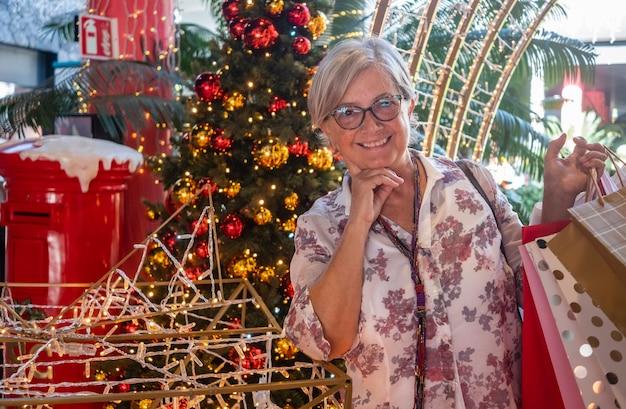 Felice donna anziana dai capelli bianchi che fa shopping per natale in un centro commerciale, in piedi vicino a decorazioni natalizie che tengono borse con regali per la famiglia e gli amici. il concetto di consumismo