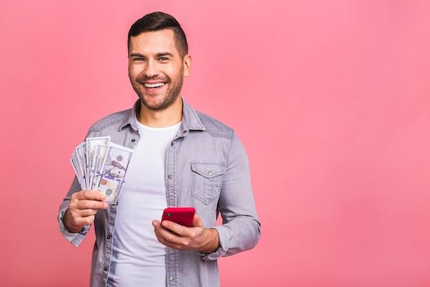 Vincitore felice uomo emozionante in maglietta casuale che tiene un sacco di soldi in valute del dollaro e telefono cellulare nelle mani