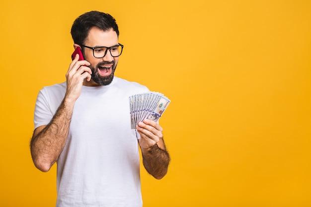 Buon vincitore! eccitato giovane uomo barbuto in casual tenendo un sacco di soldi in valuta dollaro e telefono cellulare in mani isolate sopra la parete gialla.