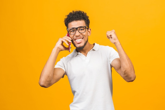 Felice vincitore. ritratto di un ragazzo afroamericano allegro che parla sul telefono cellulare
