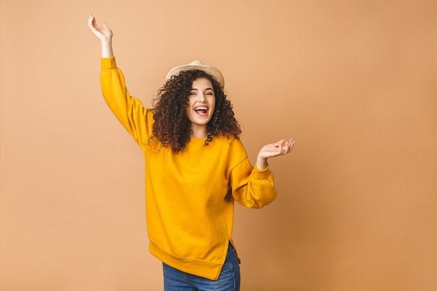 Felice vincitore. ritratto della ragazza positiva allegra che salta nell'aria che esamina macchina fotografica isolata su fondo beige. concetto di energia della gente di vita.