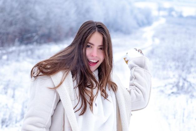 Felice inverno. giocare con la neve e divertirsi a winter park. ragazza sorridente di attività in inverno