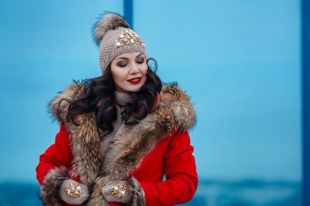 Orario invernale felice nella grande città della donna affascinante che cammina sulla strada.