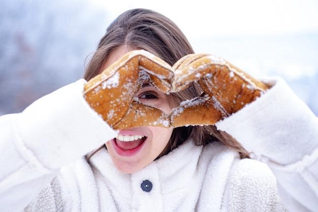 La neve felice di spettacolo della donna di inverno ha sentito. bella ragazza all'aperto. vacanze invernali. nevicata
