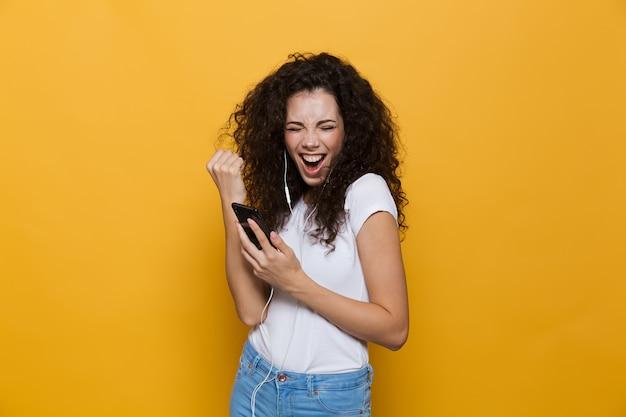 Donna felice anni '20 con i capelli ricci che ride e ascolta musica tramite cuffie e smartphone isolati su giallo
