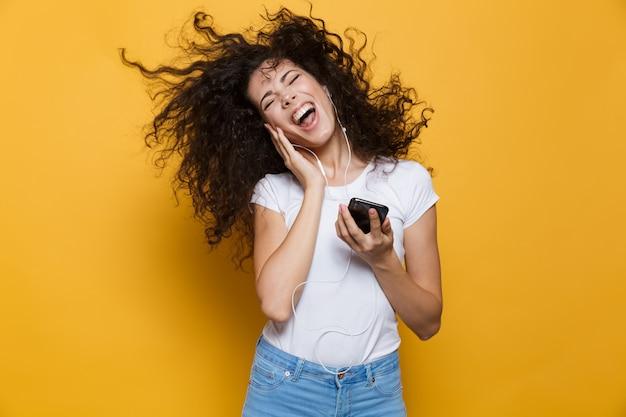 Donna felice 20s con i capelli ricci tremanti che canta mentre tiene in mano lo smartphone e ascolta la musica tramite le cuffie isolate su giallo