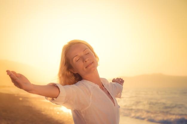 Donna felice contro il tramonto con lo sfondo del mare
