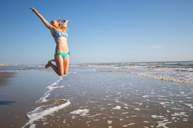 La donna felice sta giocando in riva al mare