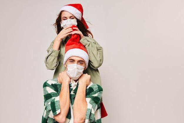 Donna felice sul retro di un uomo in una mascherina medica e salute di natale capodanno. foto di alta qualità