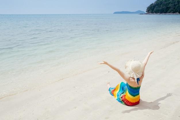 Donna felice sul cielo della spiaggia e delle nuvole.