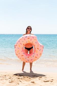 Donna felice sulla spiaggia che gioca con un anello di ciambella gonfiabile. vacanze estive e concetto di vacanza.