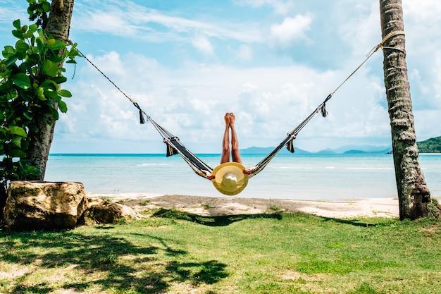 Donna felice in bikini nero che si rilassa in amaca