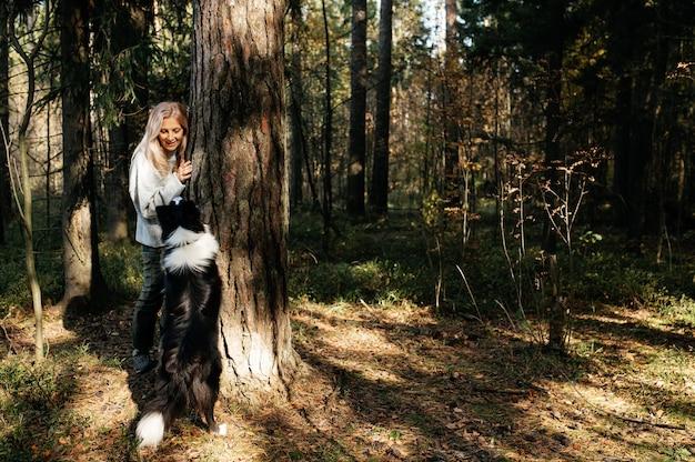 Donna felice e cane border collie bianco e nero nella foresta di autunno