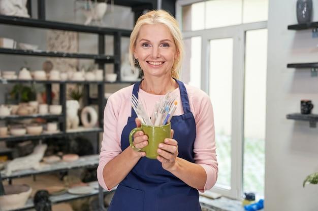 Donna felice in grembiule blu che tiene gli strumenti, spazzole per creare una ciotola di ceramica di argilla fatta a mano