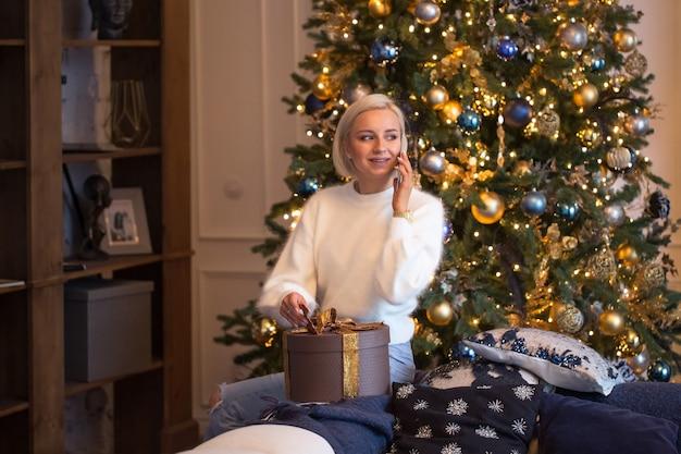 Una donna felice chiama la famiglia o il marito grata per il regalo di natale o capodanno seduta con la scatola presente vicino all'albero di natale la mattina festiva. la ragazza dice grazie per la sorpresa durante le vacanze invernali