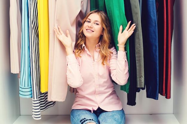 Donna felice che sceglie il guardaroba dei vestiti a casa. scelta difficile. abbigliamento, moda, lifestyle e concetto di persone. negozio di moda femminile. saldi stagionali.