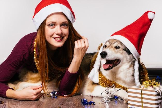 Una donna felice con un cappello di natale giace accanto a un cane