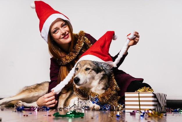 Una donna felice con un cappello di natale si siede accanto a un cane